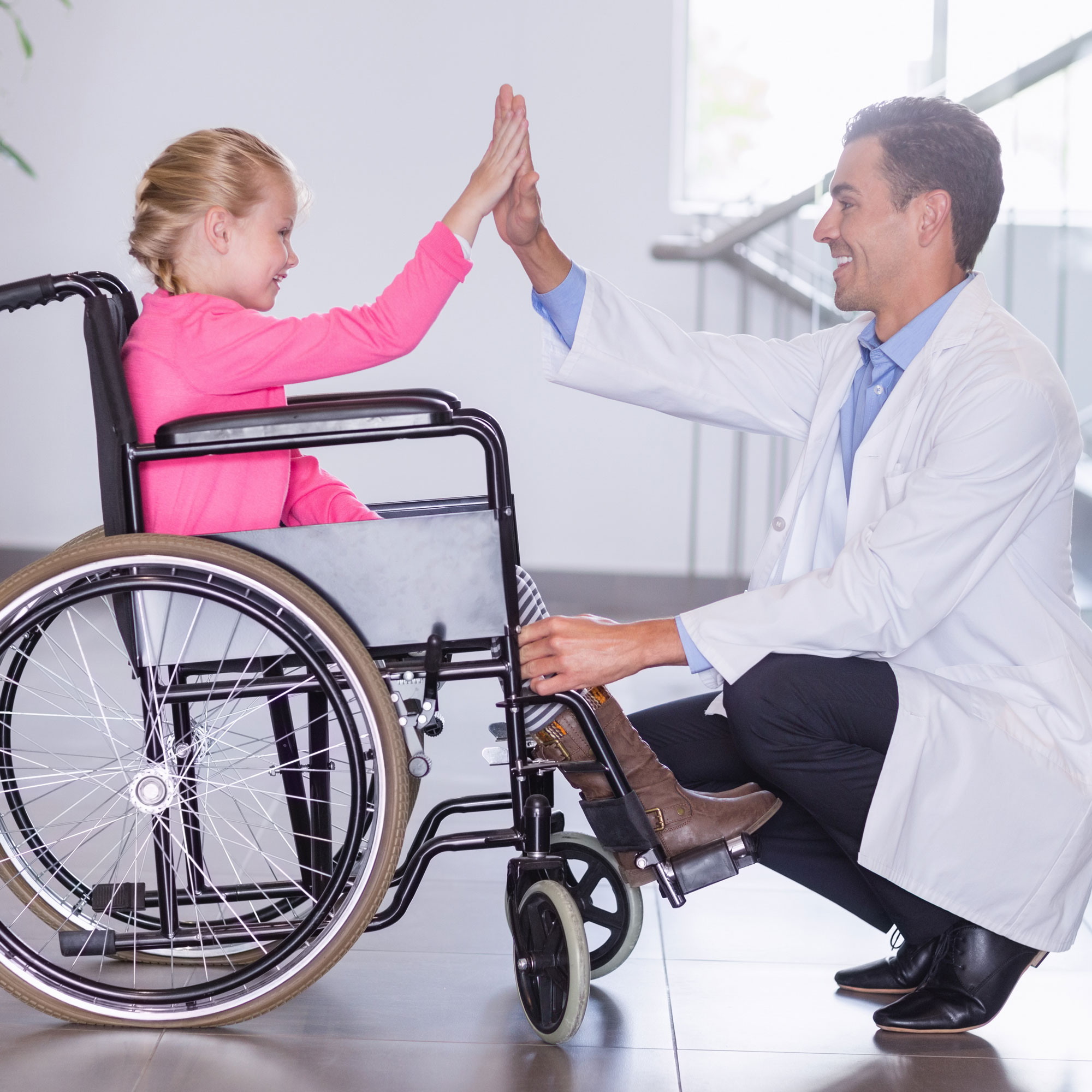 doctor-giving-high-five-to-disable-girl-5GBFPHS2